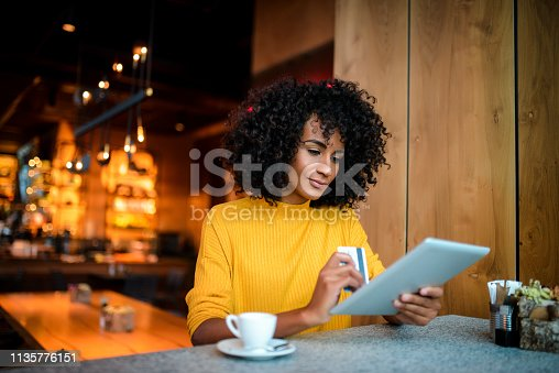 Beautiful smiling African American woman using digital tablet at the bar.