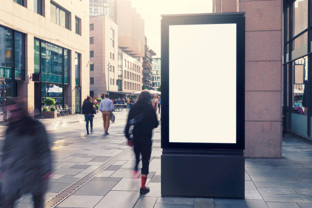 Electronic billboard in a city street An modern electronic billboard in a city street with people on the move. electronic billboard stock pictures, royalty-free photos & images