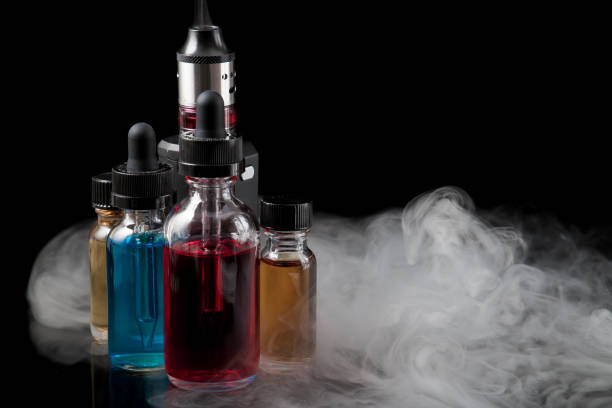 Electronic cigarette and e-liquids on black background with smoke stock photo