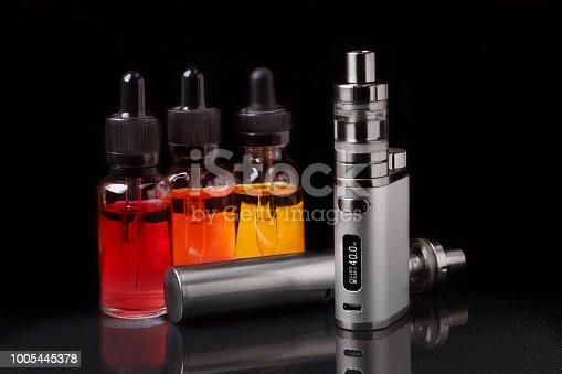 istock Electronic cigarette and vape liquids on black background 1005445378