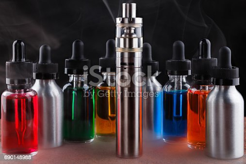 690146632 istock photo Electronic cigarette and vape liquids within vapor on granite surface and black background 690148988