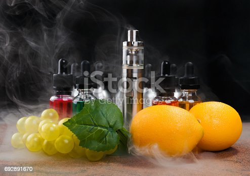 istock Electronic cigarette, lemons and bunch of grapes within vapor on black background 692891670