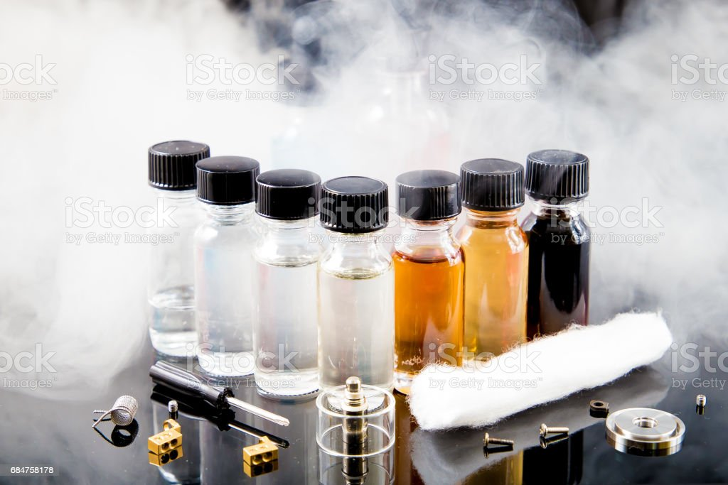 Electronic cigarette liquids with smoke on background stock photo