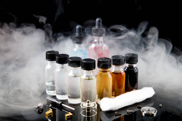 Electronic cigarette liquids with smoke on black background stock photo