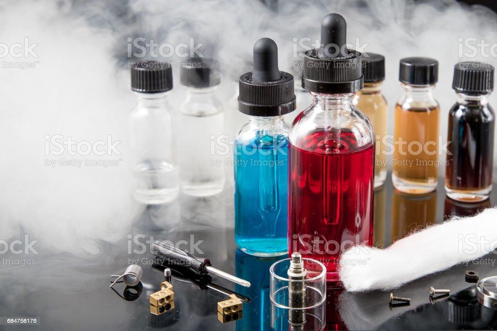 Electronic cigarette liquids with smoke on black background stock photo