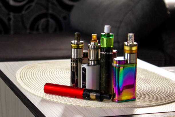 Electronic cigarette mod, advanced e-cigarette E-cigarette with blurred background. Electronic cigarette, personal vaporizer, vaping device. nicotine stock pictures, royalty-free photos & images