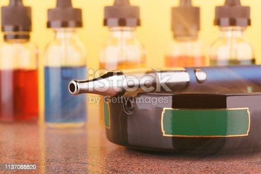 1137088939 istock photo Electronic cigarette on ashtray and bottles with vape liquid on yellow background 1137088820