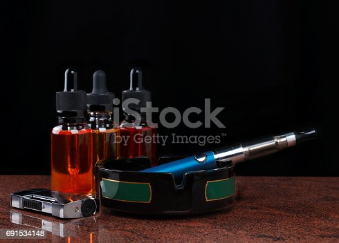 690146632 istock photo Electronic cigarette on ashtray, cigarette lighter and bottles with vape liquid on black background 691534148