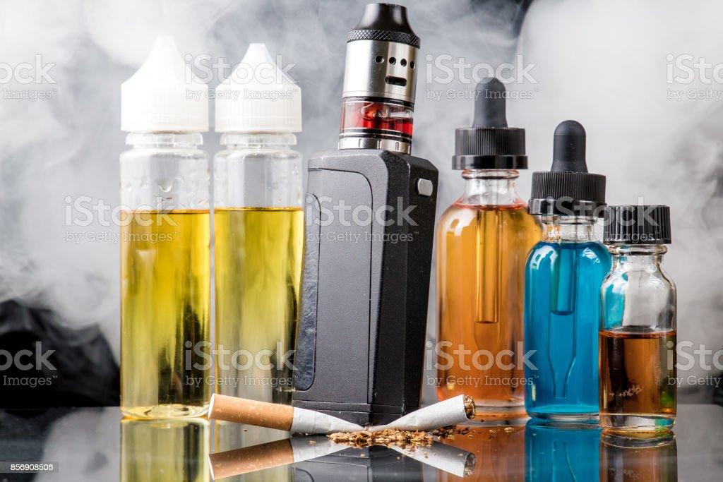 Electronic cigarette versus old tobacco cigarette in smoke cloud stock photo