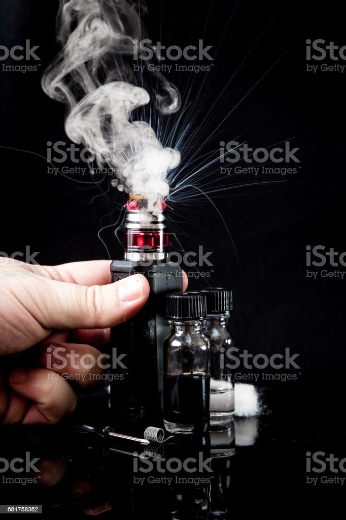 Electronic cigarette with 2 bottles and cloud of smoke stock photo