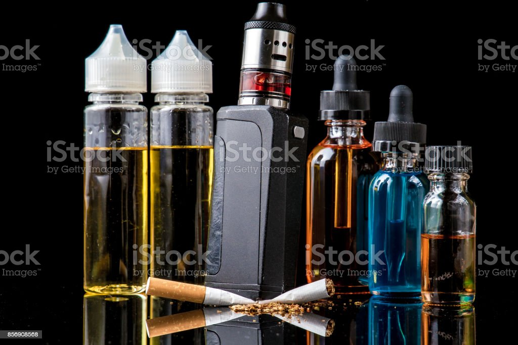Electronic cigarette with e-juice bottles versus old tobacco cigarette stock photo