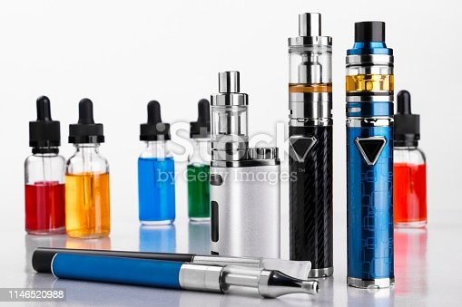 istock Electronic cigarettes and bottles with vape liquid on white background 1146520988