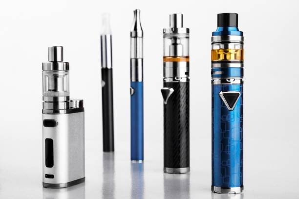 electronic cigarettes or vaping devices on white background modern electronic cigarettes or vaping devices on white background. Selective focus nicotine stock pictures, royalty-free photos & images