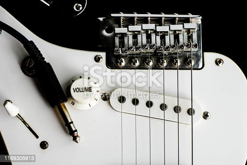 istock Electronic guitar details close up and wire cable jack. Close up black and white electronic guitar. 1169305913