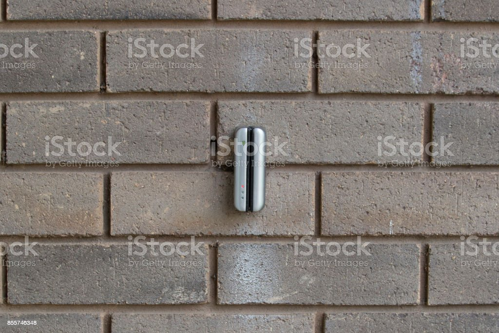 Electronic keycard reader on a brick wall stock photo