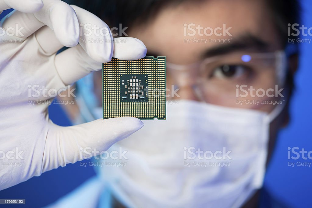 Electronic microchip Cropped image of an engineer showing a computer microchip on the foreground Adult Stock Photo