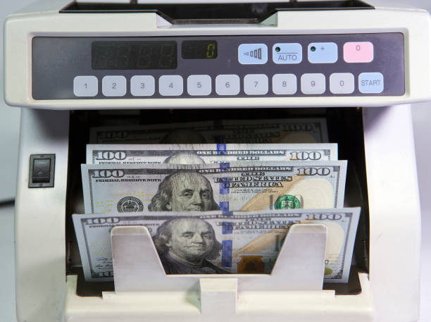 electronic money counter machine is counting is counting the American hundred-dollar (US dollars) banknotes