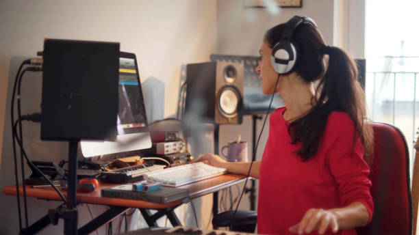 Electronic music woman A good looking Hispanic woman is composing music in her private home studio. She is using a computer & music keyboard to compose and is surrounded by musicians' equipment. synthesizer stock pictures, royalty-free photos & images
