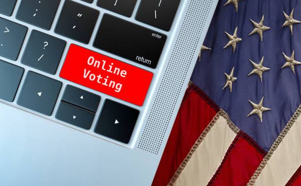 Electronic or internet voting concept (e-voting or online voting). Keyboard with red button with online voting written against usa flag. stock photo