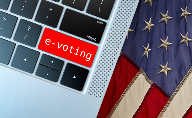 Electronic or internet voting concept (e-voting or online voting). Keyboard with red button with e-voting written against usa flag. stock photo