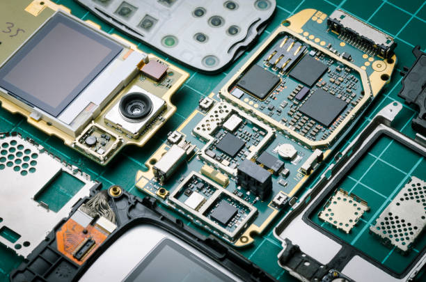 electronic parts of old mobile phone with semiconductor parts and precious metals close-up - capacitor stock photos and pictures