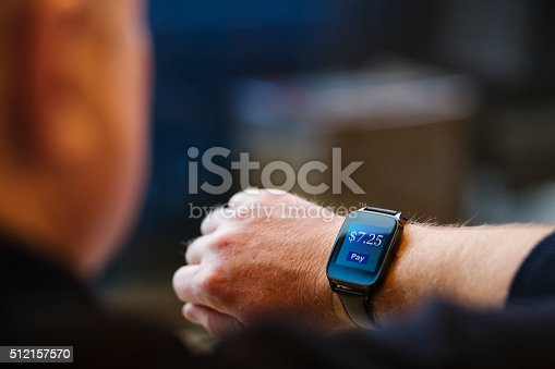 A man looks at his smart watch which is showing a prompt to make a small payment.