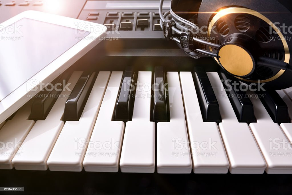 Electronic piano with headphones and tablet in studio front stock photo