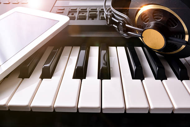 Electronic piano with headphones and tablet in studio front - Photo