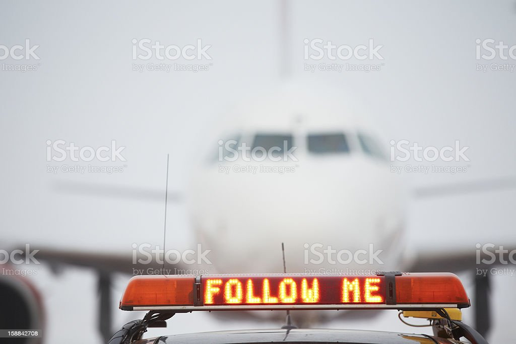 Electronic sign reading Follow Me in front of an airplane stock photo