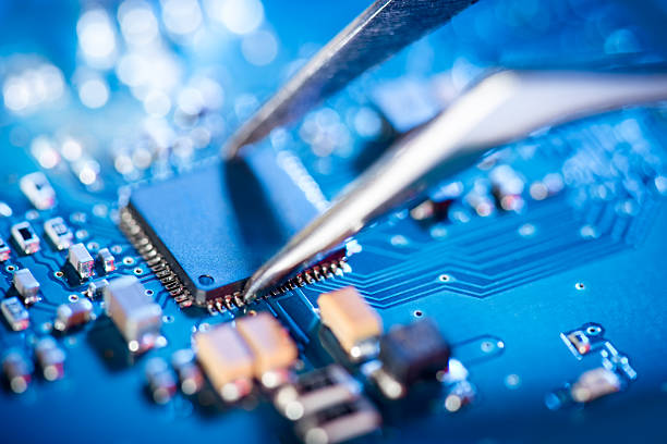 Electronic technician holding tweezers and assemblin a circuit board. Electronic technician holding tweezers and assemblin a circuit board. computer chip stock pictures, royalty-free photos & images
