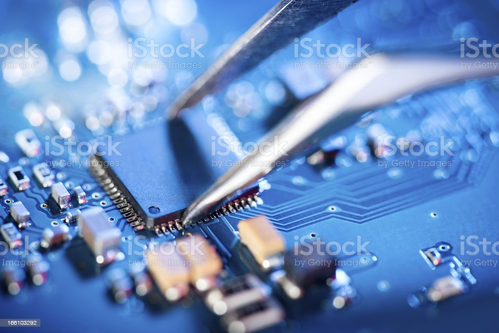 Electronic technician holding tweezers and assemblin a circuit board. stock photo