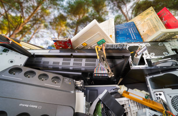 Electronic waste detail. Discarded computer hardware components on pile under trees with sunny sky stock photo