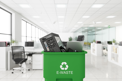 Electronic Wastes Collected In The Green Colored Garbage Bin With E-waste Symbol On It In The Office