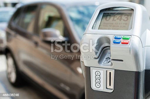 An electronic/digital parking meter has plenty of time left on it. A car can be seen in the background, parked next to the meter. The meter accepts both coins and credit cards, and buttons can be seen that control the amount of time purchased.