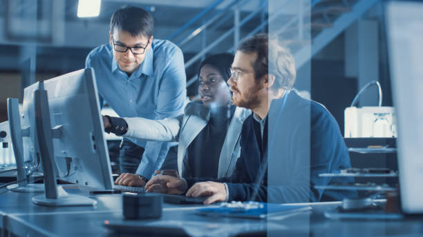 Electronics Development Engineer Working on Computer, Talks with Project Manager, Another Specialist Joins Discussion. Team of Professionals Use CAD Software for Modern Industrial Engineering Design. stock photo