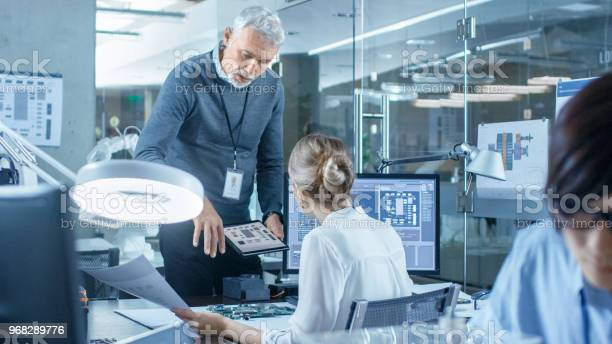 Electronics Engineer Works With Robot Manipulating Its Responses Laptop Computer Senior Engineers Talks With Chief Programmer Computer Science Research Laboratory With Specialists Working Stock Photo - Download Image Now
