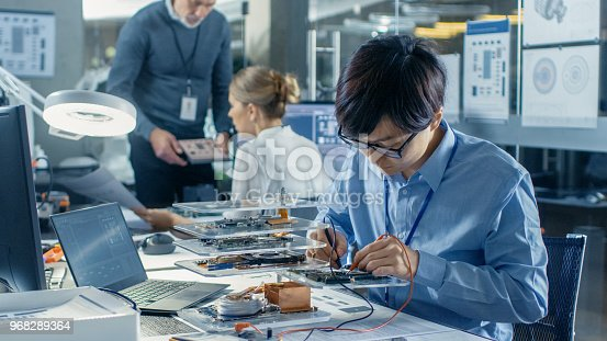 istock Electronics Engineer Works with Robot, Soldering Wires and Circuits. Computer Science Research Laboratory with Specialists Working. 968289364