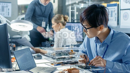 istock Electronics Engineer Works with Robot, Soldering Wires and Circuits. Computer Science Research Laboratory with Specialists Working. 968289374