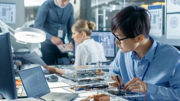 elektronica engineer werkt met robot, solderen draden en circuits. computer science research laboratory met specialisten werken. - robot engineer stockfoto's en -beelden