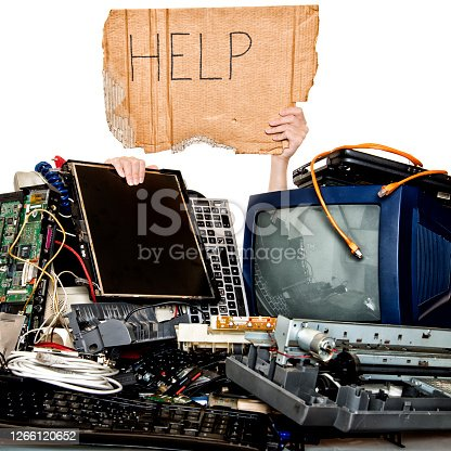 Woman holding Help sign behind a stack of obsolete computer electronic equipment. Electronic waste is sorted and prepared for further processing reusing.