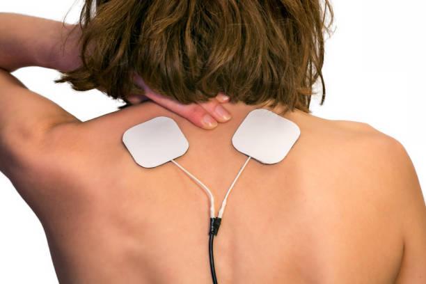 elektrotherapie bei schmerzen im schulterbereich einer frau - mit muskelkater trainieren stock-fotos und bilder