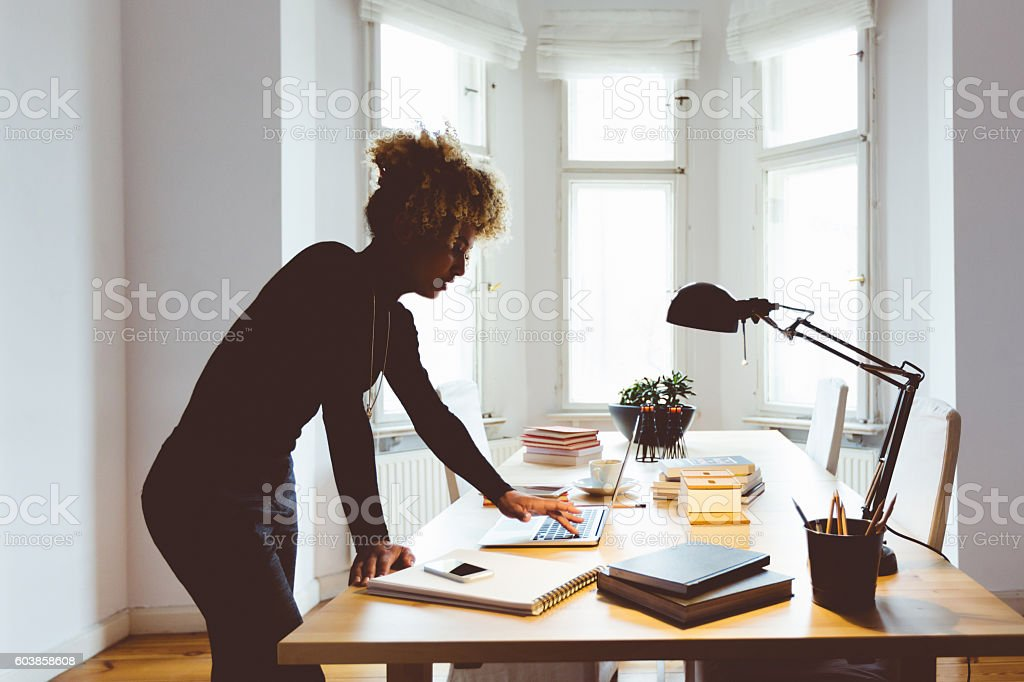 Elegance afro american young woman in a home office Elegance afro american young woman standing by the desk in a home office, using a laptop. Windows in the background. Adult Stock Photo