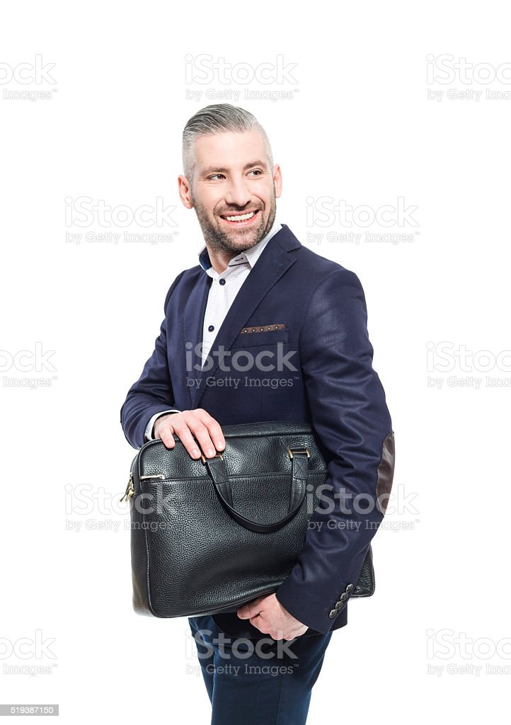Elegance bearded grey hair businessman holding bag Portrait of elegant bearded grey hair businessman standing against white background, holding briefcase. Studio shot, one person.  Adult Stock Photo