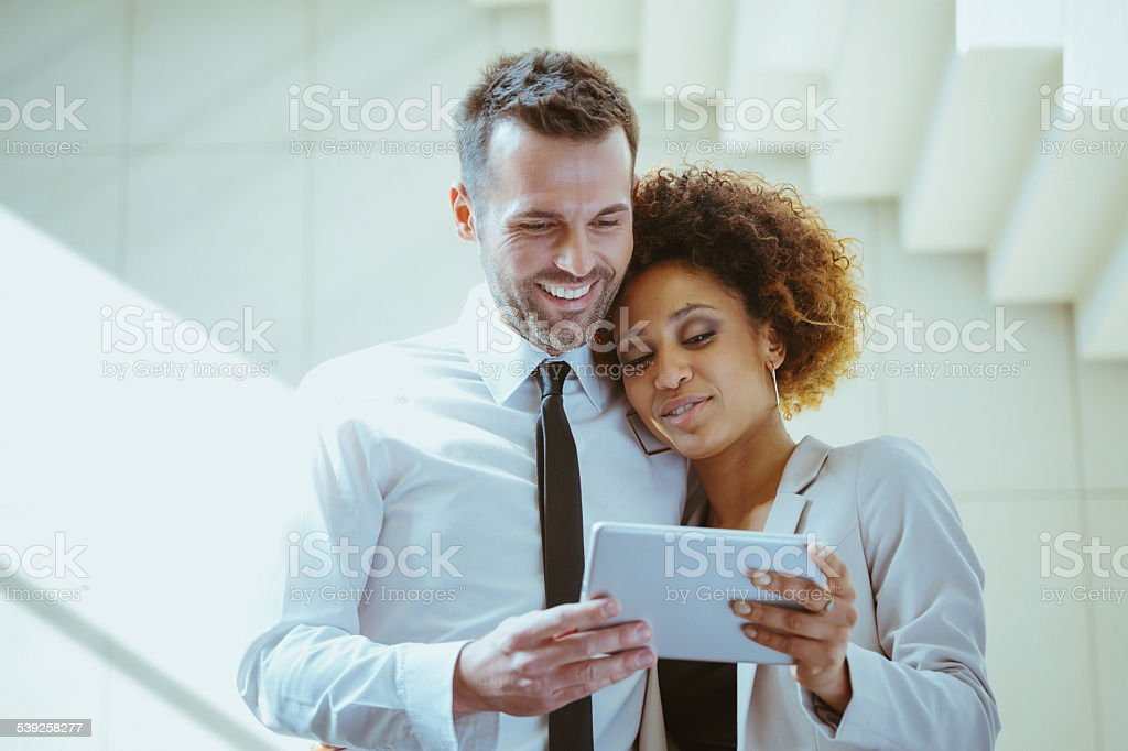 Elegance couple using a digital tablet Afro american woman embracing with attractive man, using a digital tablet together against white staircase. 2015 Stock Photo