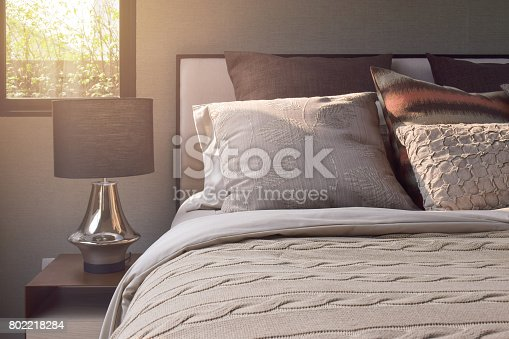 Elegance style pillows setting on classic style bedding and reading lamp on bedside table-sunlight effect