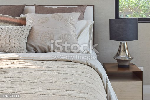 Elegance style pillows setting on classic style bedding and reading lamp on bedside table