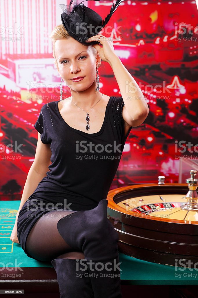 Elegance woman with lady\'s hat sitting on the casino table. Looking...