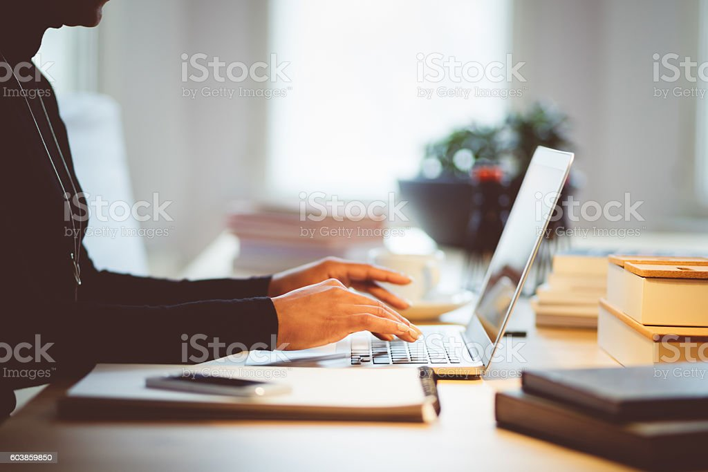Elegance woman using laptop in an office or at home Elegance woman typing on computer in an office or at home, focus on hands, unrecognizable person. Adult Stock Photo