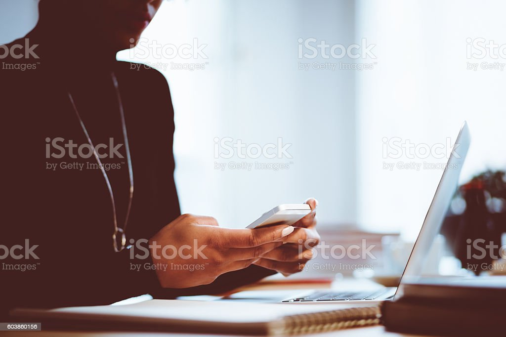 Elegance woman using mobile in an office or at home Elegance young woman texting on smart phone in an office or at home, focus on hands, unrecognizable person. Adult Stock Photo