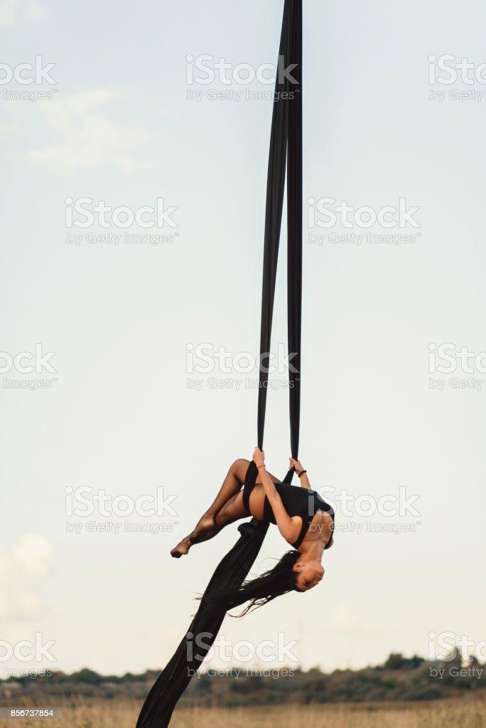 Elegancia danza de joven bella mujer con seda aérea sobre un fondo de cielo. Vuelo deporte yoga - foto de stock
